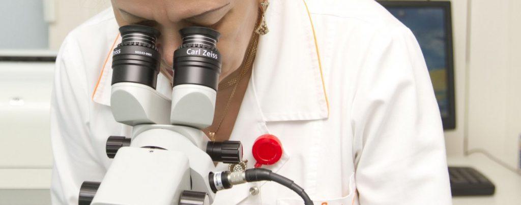 Врач у микроскопа
